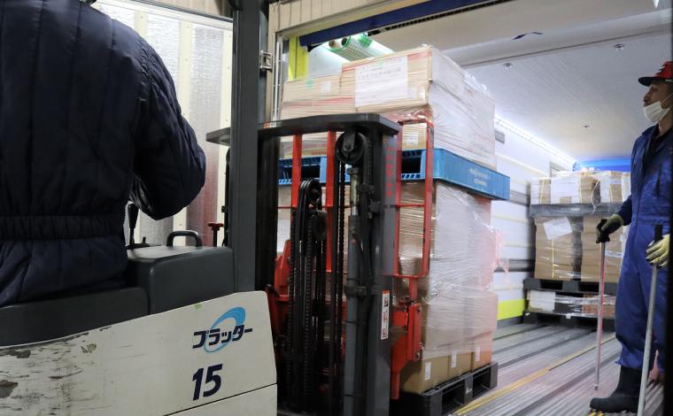 トラックの荷台から荷物を次々とフォークリフトが運びます